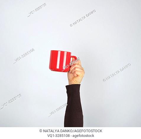 red ceramic cup in a female hand on a white background, hand is raised up