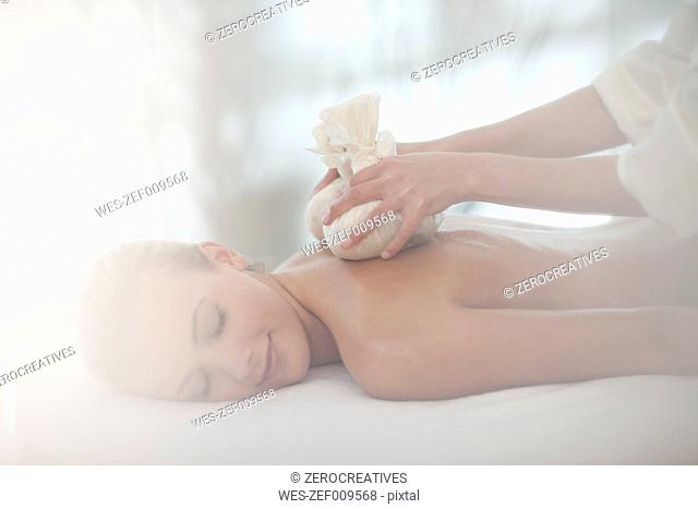 Masseuse placing aromatherapy sachets on woman's back