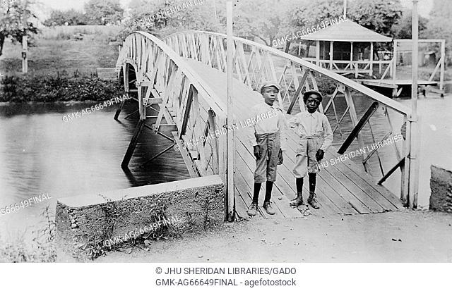 Full length standing portrait of two African American boys, wearing light shirts, dark pants and caps, standing on bridge, neutral expressions, 1920