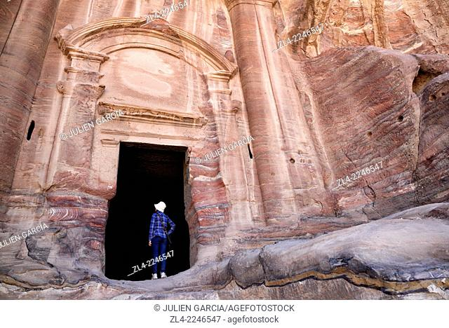 Woman at the entrance of the Renaissance Tomb carved in the mountain. Jordan (Hashemite Kingdom of), Ma'an Governorate (Maan), ancient city of Petra