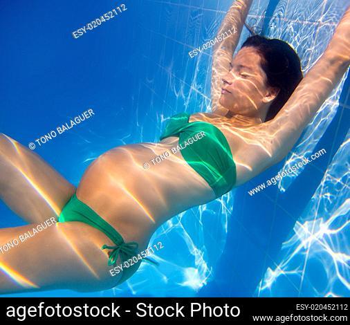 Beautiful pregnant woman underwater blue pool