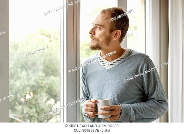 Man at home, looking out of window, holding hot drink