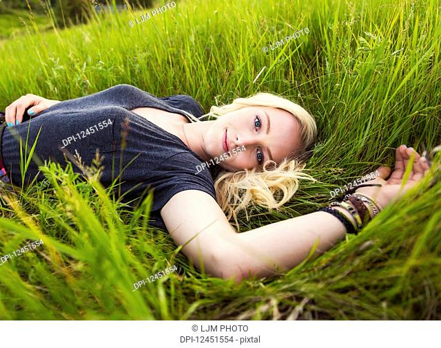 Portrait of a young woman with long blond hair laying on the grass in a park; Edmonton, Alberta, Canada