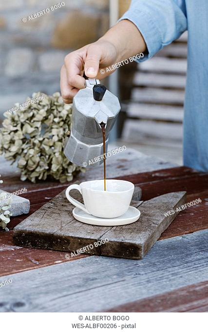 Italy, woman pouring espresso into cup on breakfast table, partial view