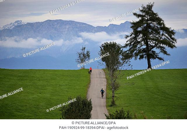 24 September 2019, Bavaria: A jogger and her dog run over a hilltop in front of a cyclist under a cloudy sky. Photo: Karl-Josef Hildenbrand/dpa