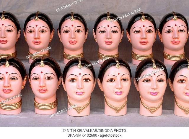 Many idols of Goddess Gauri ; richly painted head up to neck kept for sell for Ganapati festival at Pune ; Maharashtra ; India