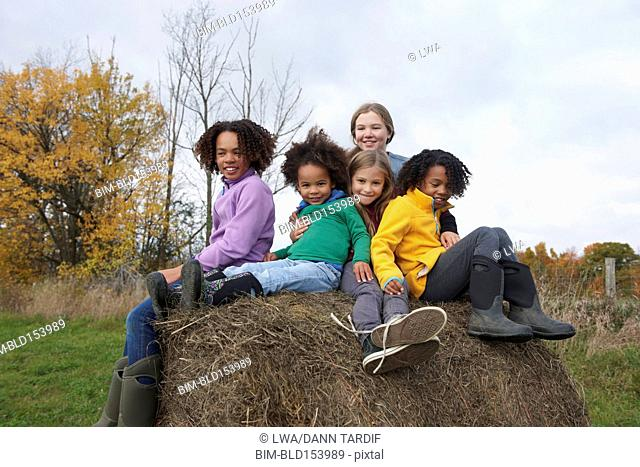 Children playing on hay bale in field