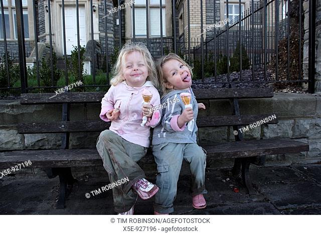 6 year and 5 year girls sitting on bench eating icecream and making silly faces