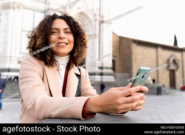 Smiling woman with smartphone at Santa Croce church, Florence, Italy
