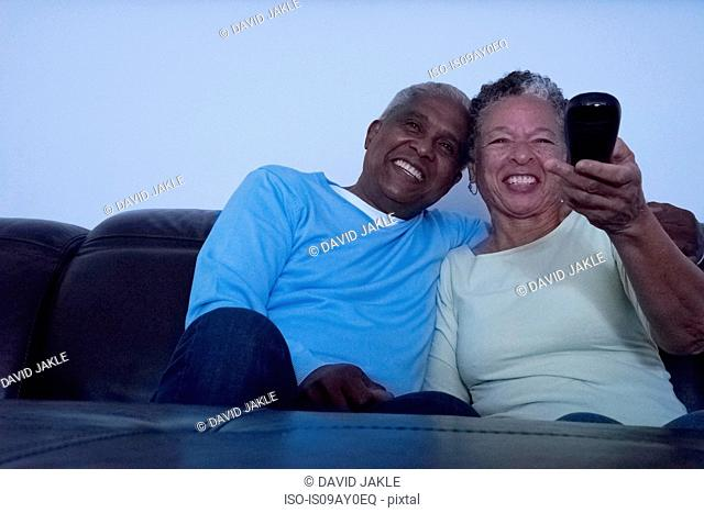Senior couple sitting on sofa at night, watching television, woman holding remote control