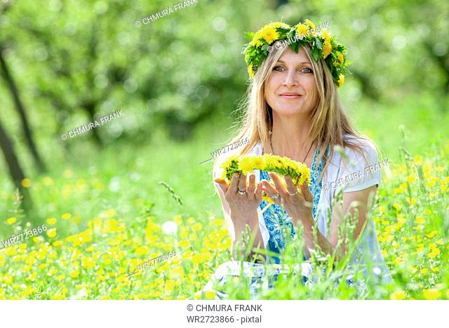 woman with flower wreath siting in a spring meadow