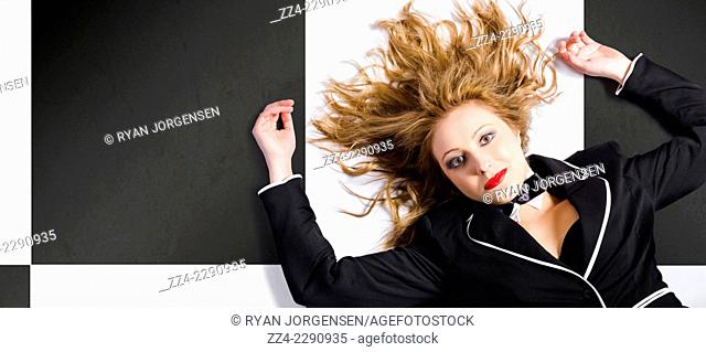 Horizontal portrait of a beautiful blond girl with healthy long hair lying down with wavy hairstyle on tiled background. hair care concept