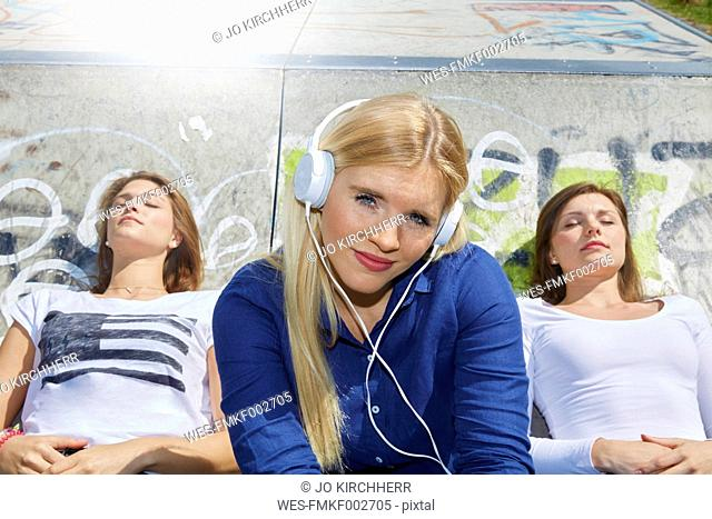 Smiling young woman listening music with headphones while her friends relaxing in the background