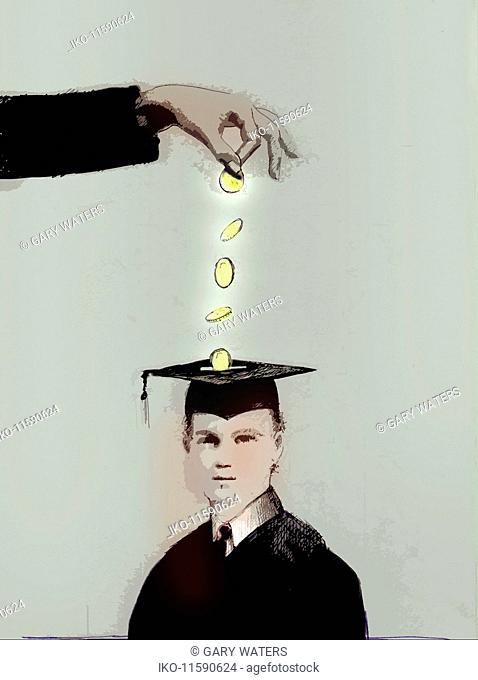 Hand dropping money into slot in mortarboard money box on student