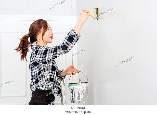 Female interior designer painting