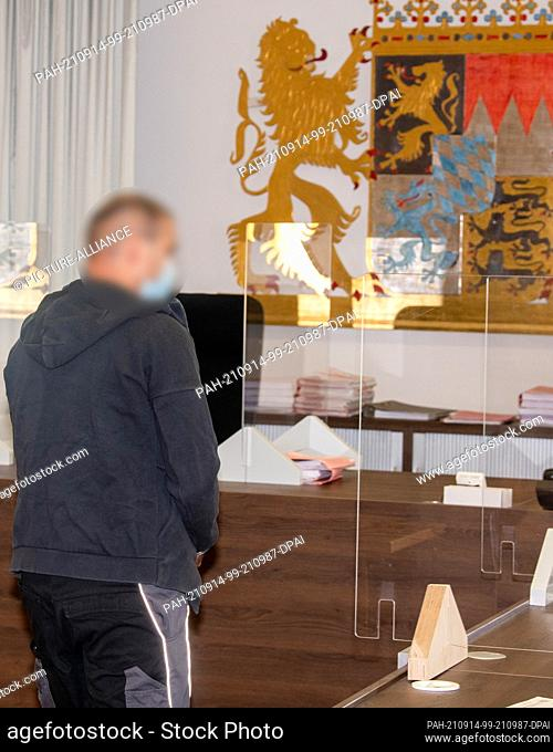 14 September 2021, Bavaria, Memmingen: In the district court, a man walks towards the Bavarian coat of arms in the jury room