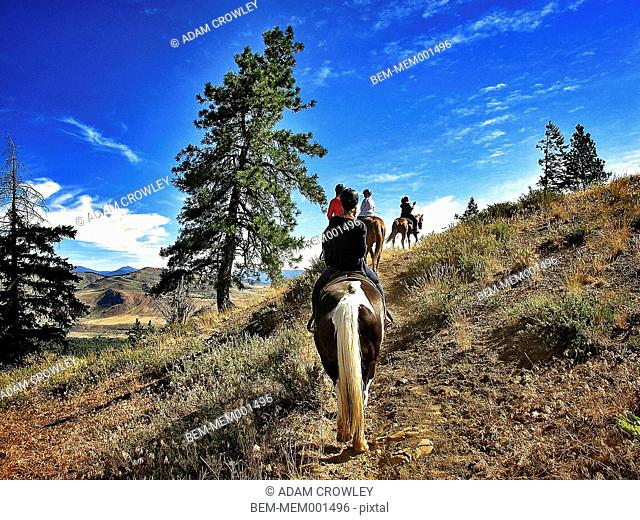 People riding horses on dirt path in remote landscape