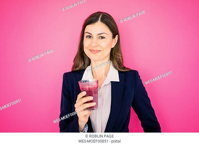 Portrait of smiling businesswoman in front of pink wall holding glass of juice