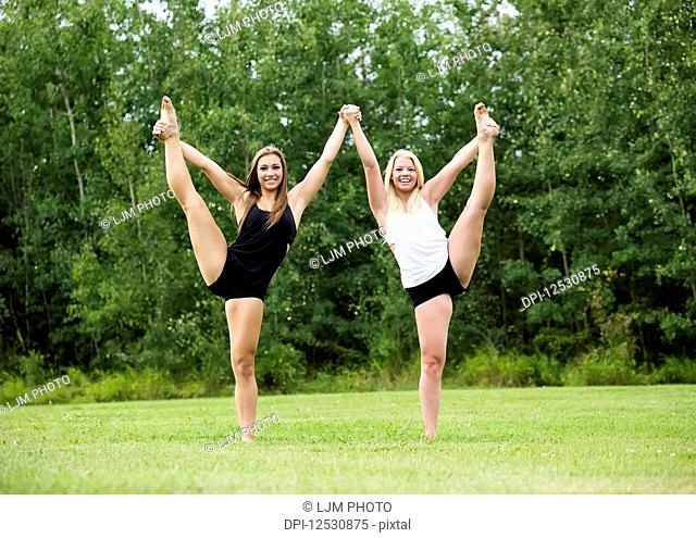 Two Teenage Gymnists Practicing Their Routines Outdoors In A Park; Edmonton, Alberta, Canada