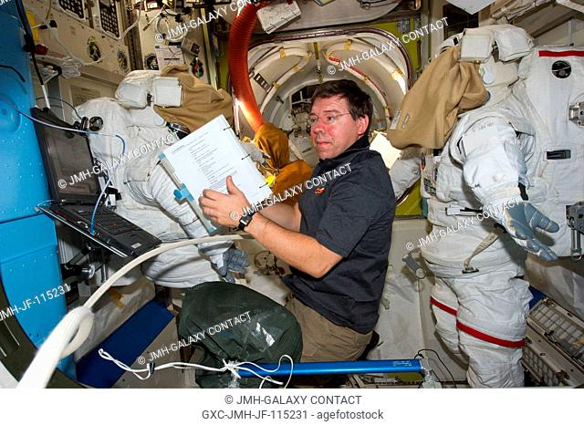NASA astronaut Michael Barratt, STS-133 mission specialist, is pictured between two Extravehicular Mobility Unit (EMU) spacesuits in the Quest airlock of the...