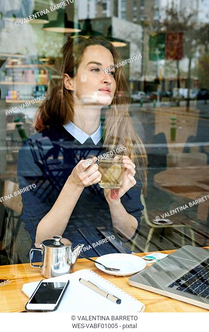 Young woman with laptop and cup of tea in a cafe