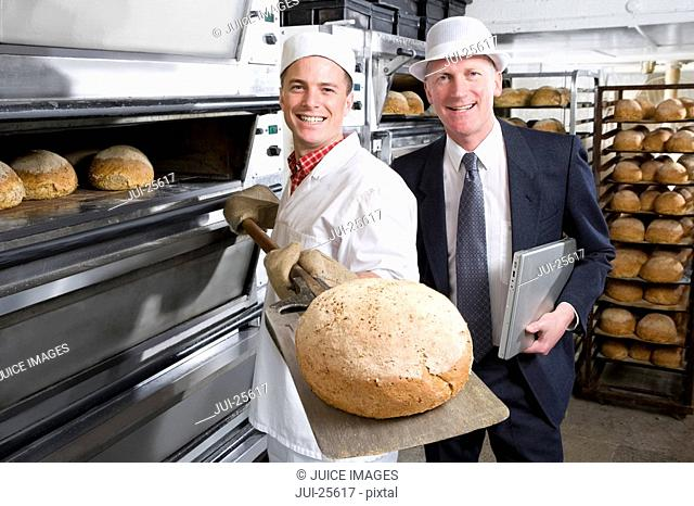 Inspector with baker as he removes bread from oven