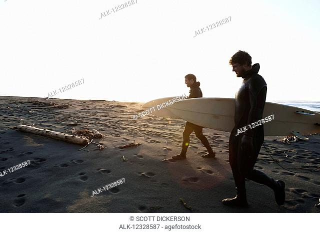 Two surfers walking on a beach with their boards, Southeast Alaska; Yakutat, Alaska, United States of America