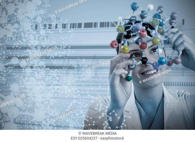 Composite image of happy female scientist holding molecular model
