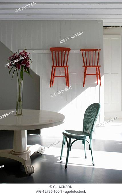 Kitchen with white painted pedestal table, Lloyd Loom chair and shaker style hanging chairs