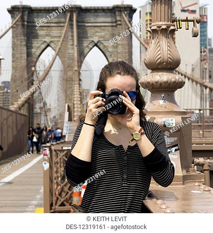 A young woman holds a camera to take a photograph, pointing at the camera, on the Brooklyn Bridge; New York City, New York, United States of America