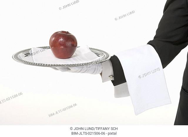 Butler holding a silver tray with an apple