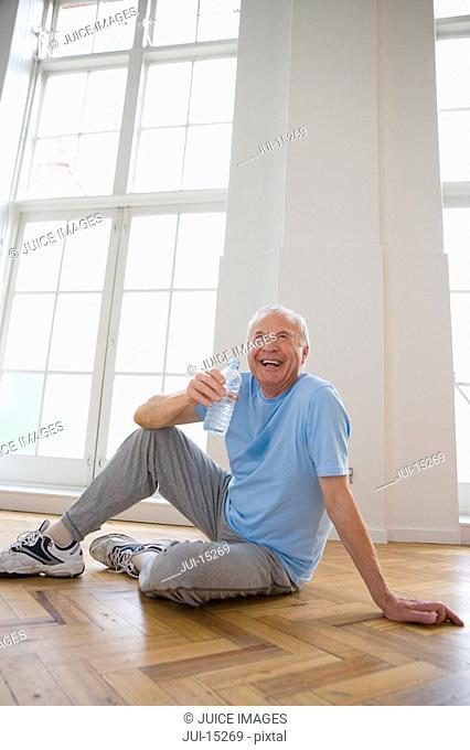 Senior man with water bottle, smiling