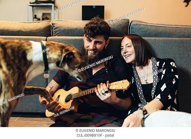 Couple sitting on apartment floor holding dog's paw