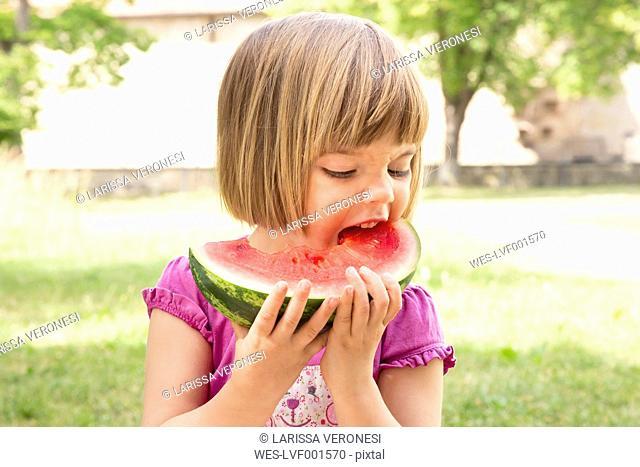 Portrait of little girl eating watermelon