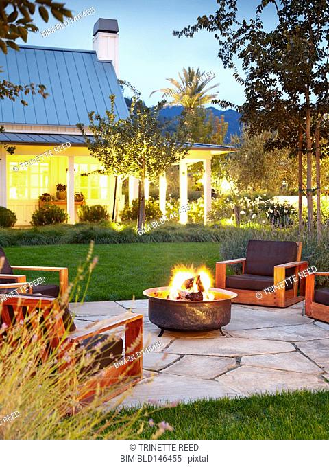 Chairs around fire burning in fire pit at luxury hotel