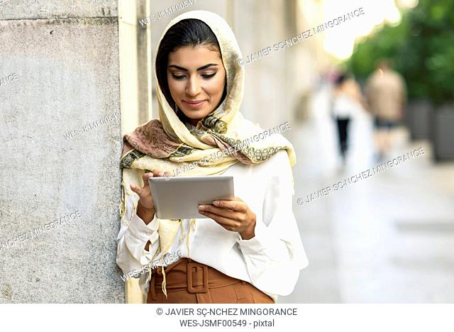 Spain, Granada, young muslim woman wearing hijab using tablet outdoor