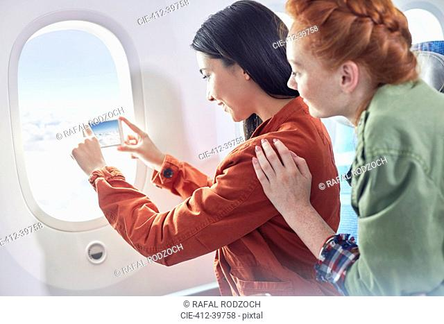 Young women friends using camera phone at airplane window
