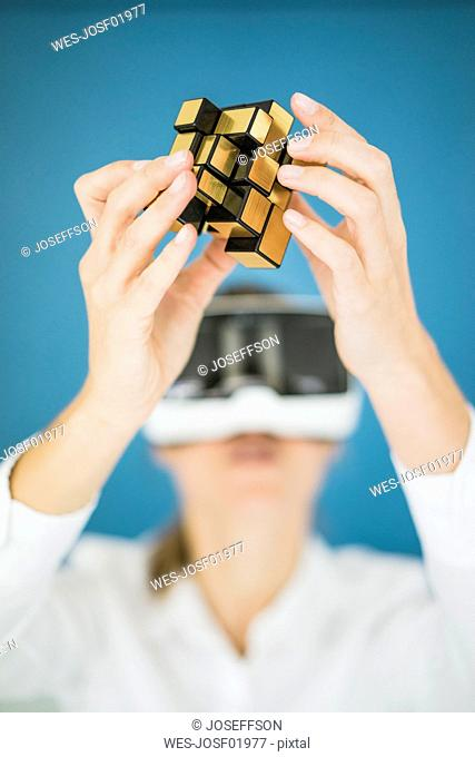 Businesswoman wearing VR glasses holding cubical structure