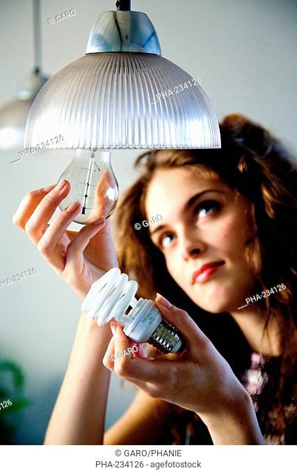 Woman putting an energy saving lightbulb