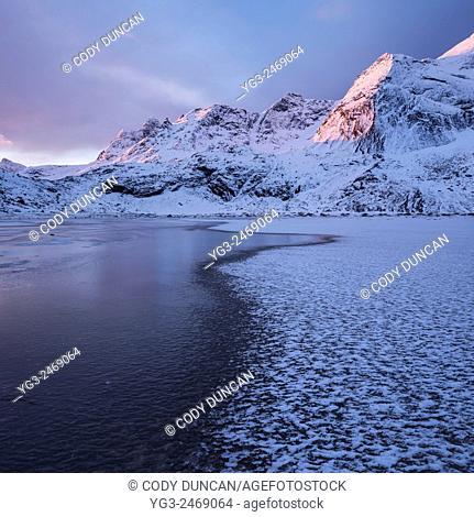 Winter sunrise over snow covered mountain peaks rising above frozen sand of Bunes beach, Moskenesøy, Lofoten Islands, Norway