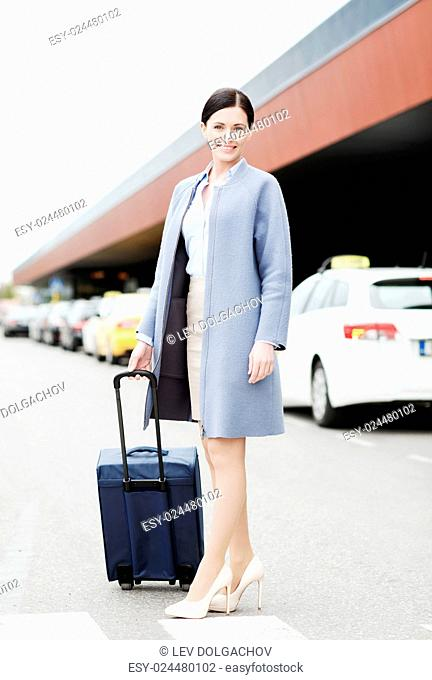 travel, business trip, people and tourism concept - smiling young woman with travel bag over taxi at airport terminal or railway station