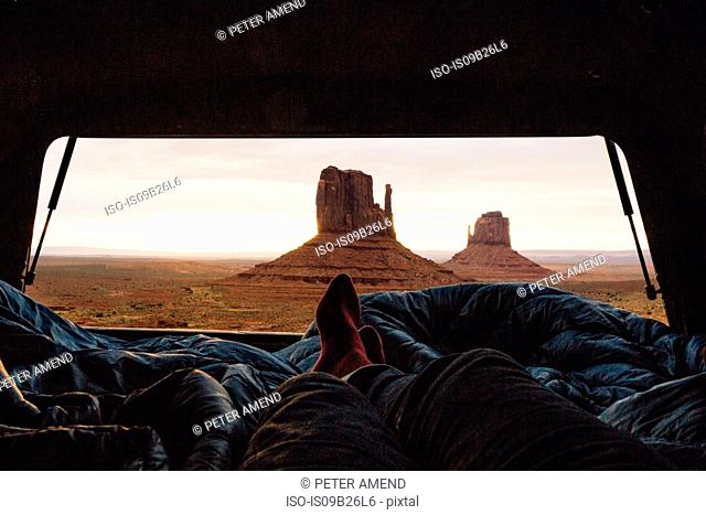 Male legs and feet relaxing inside four wheel drive with view of sandstone buttes from car boot, Monument Valley, Arizona, USA