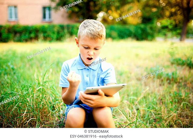 Young kid sittingin the courtyard and playing a game on tablet pc