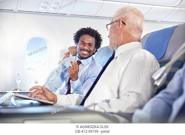 Smiling businessmen exchanging business cards on airplane