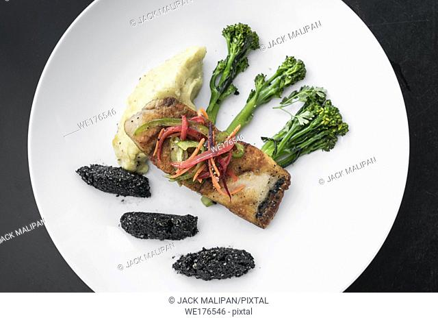 red snapper fish fillet with vegetables and black rice with black sesame seeds asian modern fusion dish in melbourne australia restaurant