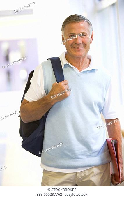 Man standing in corridor with backpack high key