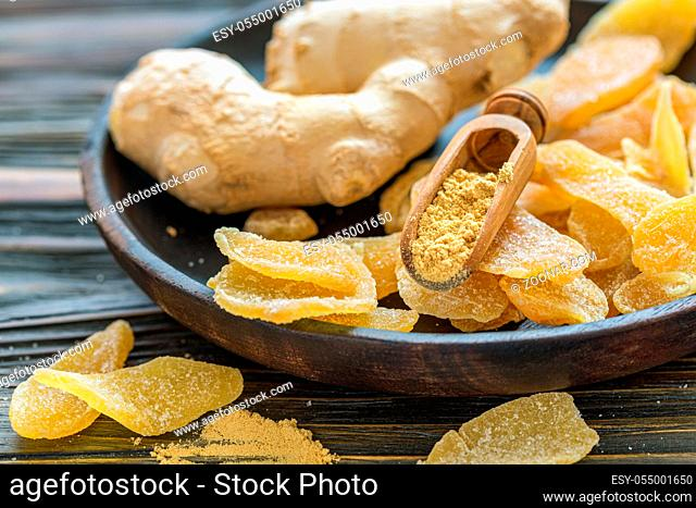 Dish with ginger root, spicy ginger candied fruit and wooden scoop with ground ginger, selective focus