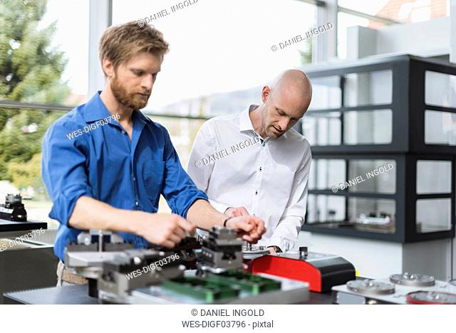 Two men working on product in company