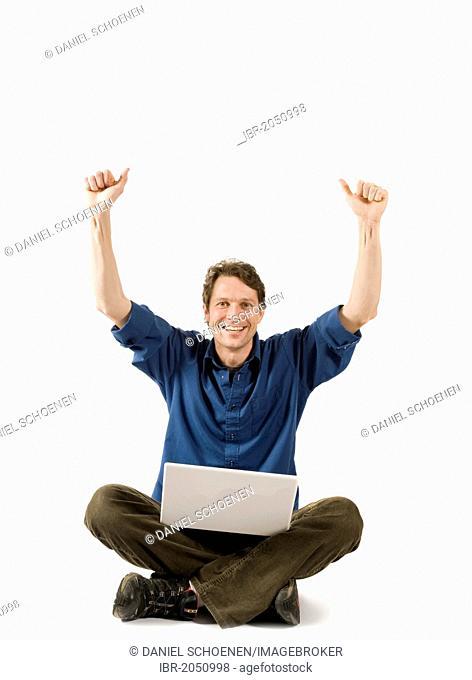 Man sitting cross-legged on floor with a laptop, cheering
