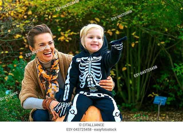 Trick or Treat. smiling young mother and daughter on Halloween at the park pointing at something